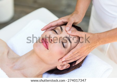 Brunette receiving head massage at the spa - stock photo