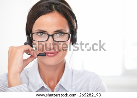 Brunette receptionist with glasses speaking on the headphones while smiling and looking at you - copyspace - stock photo