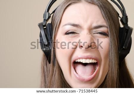 Brunette screaming while listen music on headphones - stock photo