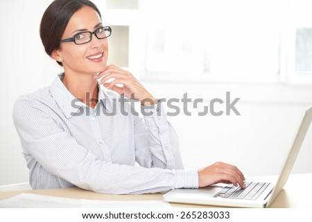 Brunette secretary in blue blouse using her laptop on desk and looking at you - stock photo