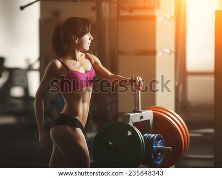 Brunette sexy fitness girl in pink sport wear with perfect body in the gym posing before training set. Attractive fitness woman, trained female body, lifestyle portrait, caucasian model - stock photo