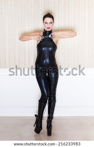 Brunette sexy woman in latex catsuit showing handcuffs, bdsm - stock photo