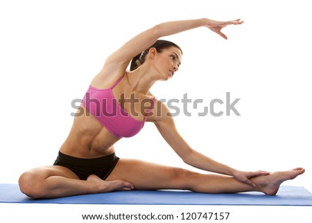 brunette sitting down and stretching her legs on white background - stock photo