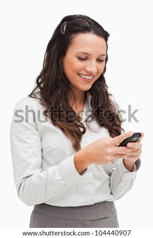 Brunette smiling while looking her text message against white background - stock photo