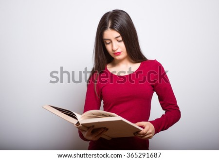 brunette student girl with books, reads or keeps in a red dress, studio isolated portrait emotions - stock photo