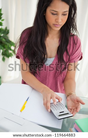 Brunette student taking a calculator to do her homework - stock photo