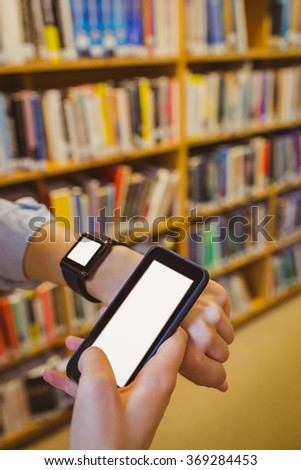 Brunette student using her smart watch and smartphone in library - stock photo