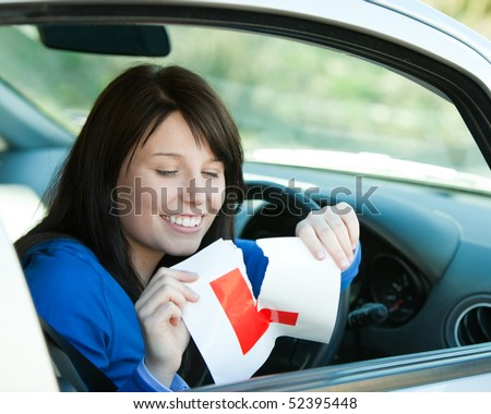 Brunette teen girl sitting in her car tearing a L-sign after having her driver's licence - stock photo