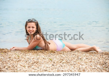 Brunette tourist lying in beach sand tanning happy in summer vacation - stock photo