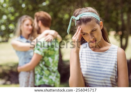 Brunette upset at seeing boyfriend with other girl on a summers day - stock photo