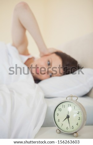 Brunette waking in her bed in a bedroom with an alarm clock on foreground - stock photo