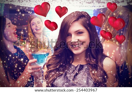 Brunette with cocktail against floating love hearts - stock photo