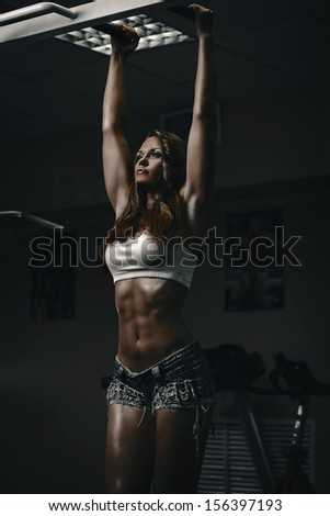 Brunette woman doing pull ups in gym - stock photo