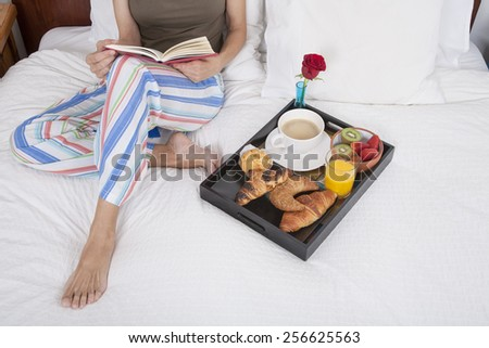 brunette woman green shirt striped pajama pants sitting on white bed reading red book with breakfast tray croissants orange juice strawberry kiwi cupcake red rose flower - stock photo