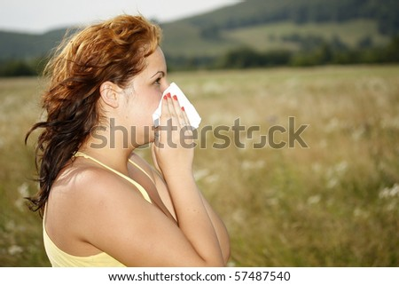 brunette woman having a pollen allergy in the nature - stock photo