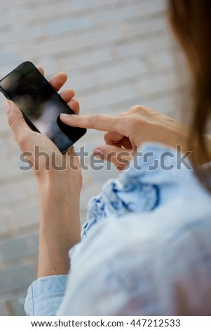 Brunette woman holding smartphone. Gadget with blank copy space - stock photo