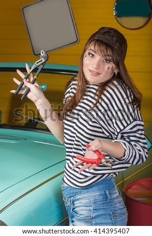 brunette woman in a cap and a striped sweater holding empty or full canister of gasoline in the garage near the retro car. Repair, service, men's work, help, handyman - stock photo