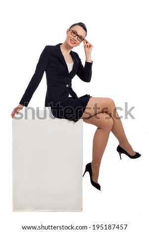 brunette woman in black skirt and jacket sitting on the white cube over white background - stock photo