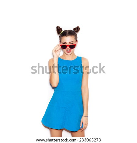 Brunette Woman in sunglasses showing tongue. Beauty girl with bright makeup hairstyle with horns in a blue dress having fun. On a white background, not isolated - stock photo
