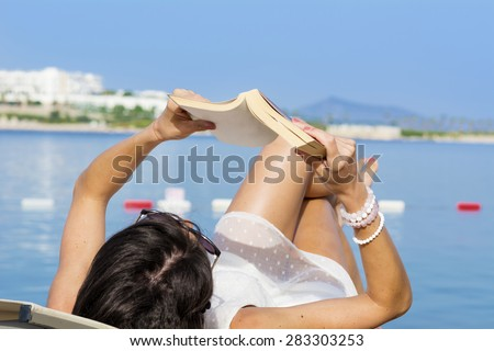 brunette woman lying on the beach and reading a book on a sea background - stock photo