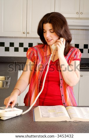 Brunette Woman Making A Phone Call From Her Kitchen - stock photo