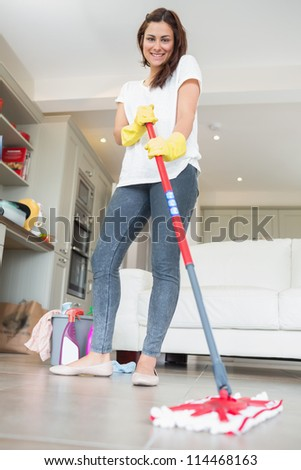 Brunette woman mopping the floor while smiling - stock photo