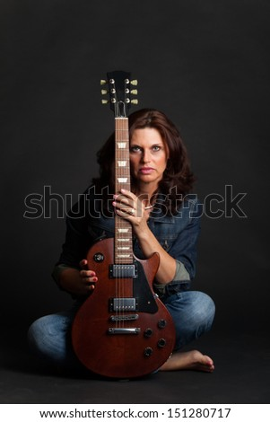 brunette woman on black with a guitar  - stock photo