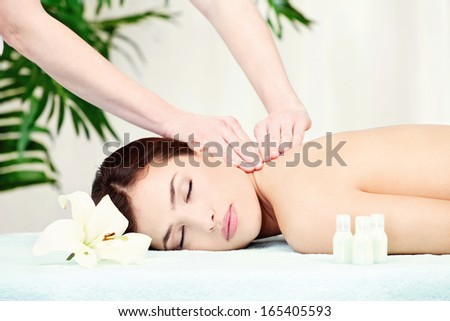 Brunette woman on neck massage in spa center - stock photo