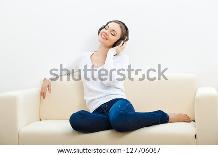 brunette woman on the sofa listening to music with closed eyes - stock photo