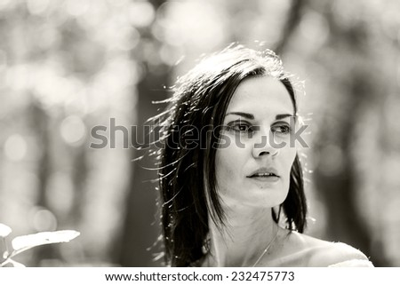 Brunette woman posing in the forest with beautiful light. Black and white photography  - stock photo