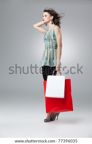 brunette woman shopping red white bags wind - stock photo