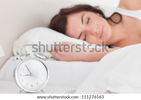 Brunette woman sleeping in the morning in her bedroom - stock photo