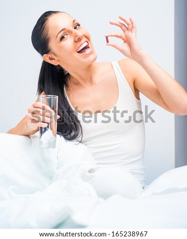 Brunette woman taking a pill sitting on bed at home - stock photo