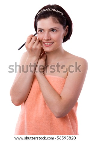 Brunette woman using eyeliner on her eyes. Black cosmetic pencil. Beautiful women eye close-up. Application of eyeliner. Young woman doing a make-up - stock photo