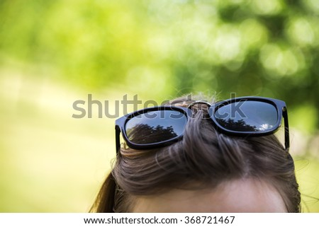 Brunette woman wearing black sunglasses on top of her head - stock photo