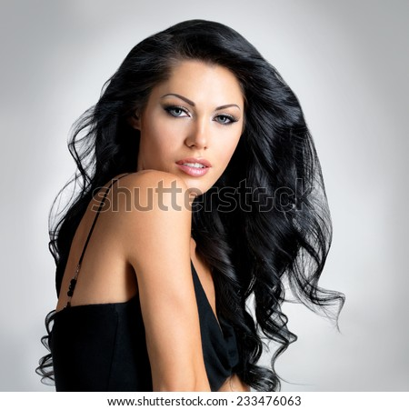 Brunette woman with beauty long brown hair - posing at studio on gray background - stock photo