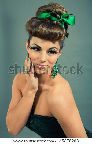 brunette woman with green jewelery and accssesoires on grey background - stock photo