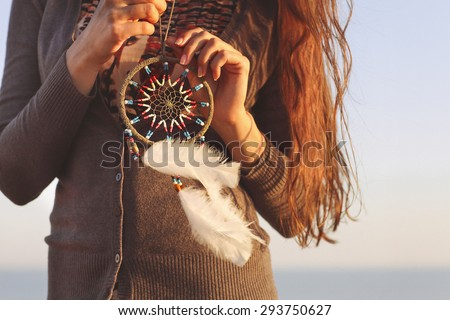 Brunette woman with long hair holding dream catcher in her hands - stock photo