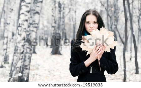 Brunette woman with maple leaves. Bright white autumn forest background. - stock photo