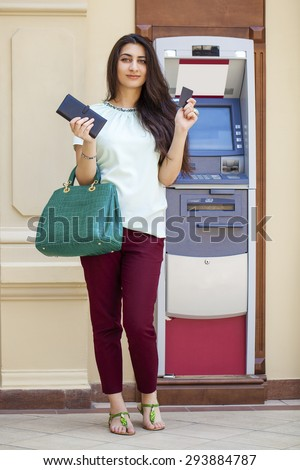 Brunette young lady using an automated teller machine . Woman withdrawing money or checking account balance - stock photo
