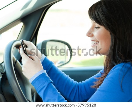 Brunette young woman sending a message with her mobile phone sitting in her car - stock photo