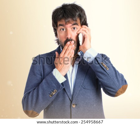 Brunetteman talking to mobile over white background - stock photo
