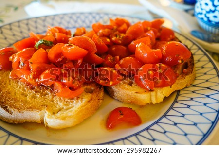 Bruschetta is an antipasto (starter dish) from consisting of grilled bread rubbed with garlic and topped with olive oil and salt.  - stock photo
