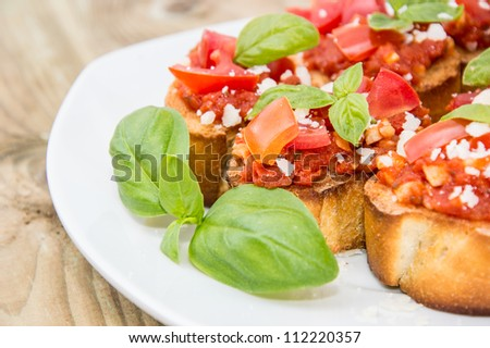 Bruschetta on a plate against wooden background - stock photo
