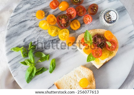 Bruschetta with a Mix of Red, Orange and Yellow Cherry Tomatoes - stock photo