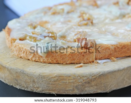 bruschetta with blue cheese and walnuts on old wooden plank, very shallow dof, selective focus on walnut - stock photo