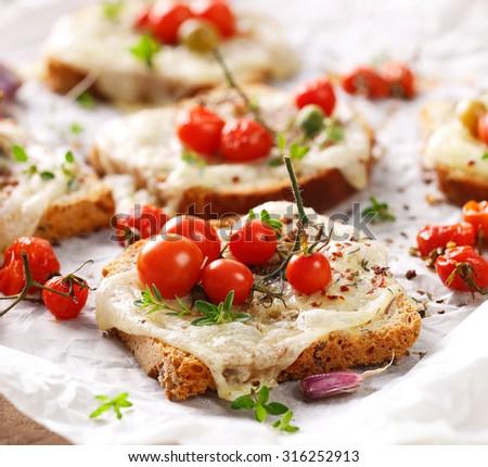 Bruschetta with cheese, cherry tomatoes and herbs - stock photo
