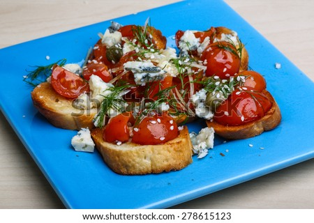 Bruschetta with cheese, tomato, olive oil and capers - stock photo