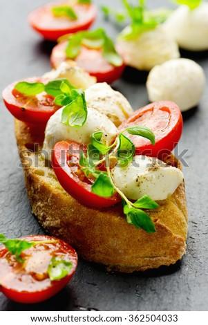Bruschetta with cherry tomatoes, mozzarella cheese and marjoram - stock photo