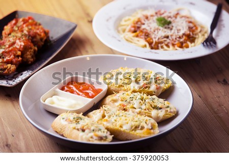 Bruschetta with chicken, tomato, parmesan and cheddar cheese with romantic candle light dinner on wooden table background, for appetizer with spaghetti bolognese and hot spicy chicken wings on back - stock photo
